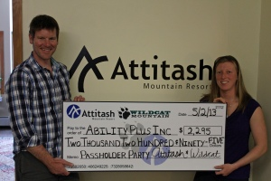 AbilityPLUS Inc. Program Director Liz Stokinger accepts a $2,295 donation from Attitash and Wildcat Mountain Director of Marketing Thomas Prindle.